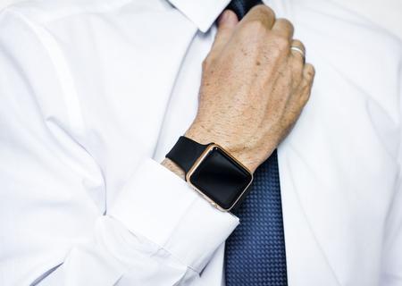Hand with smartwatch adjust necktie Banco de Imagens