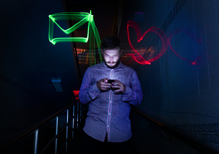 Closeup of a man using mobile phone night time with long exposure icons