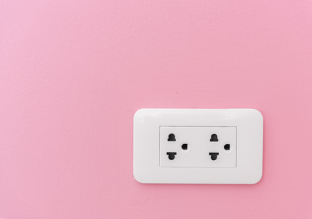 Electricity plug supply on pink wall
