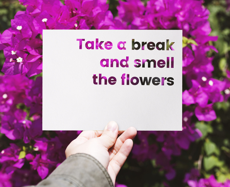 Hand holding paper with take a break and smell the flowers word cut out