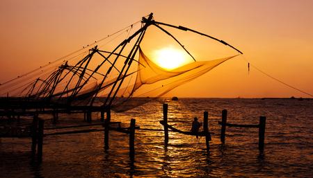Indische mens die onder de grote Chinese netten in Cochin, Kerela, India vissen.