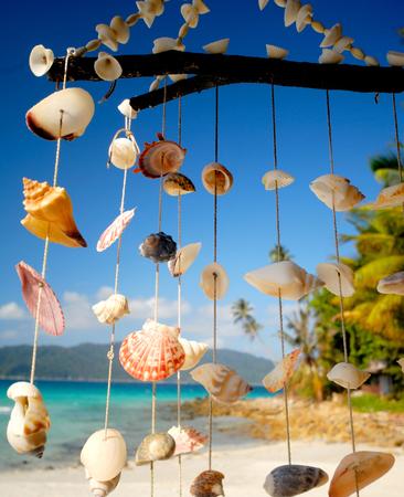 Sea shell chime overlooking a tropical lagoon. Фото со стока