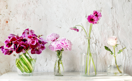 A row of vases with pink flowers