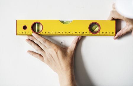 벽에 통치자를 측정하는 수리공
