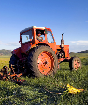 Mongolian farmer driving his tractor in the field. Stock Photo