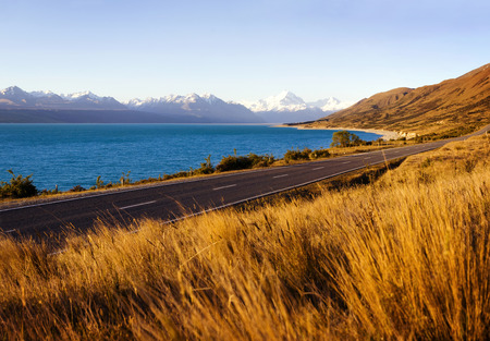 Country road with amazing scenery of lake and a mountain range.