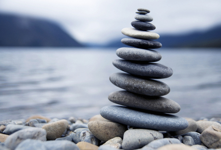Zen balancing pebbles next to a misty lake. Stock Photo
