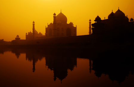 Sunset silhouette of a grand Taj Mahal.