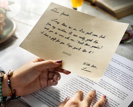 여자 손은 엽서를 잡고있다.