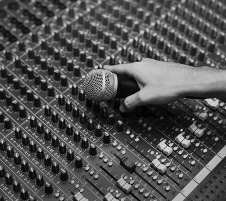 Hand with microphone on a sound mixer grayscale