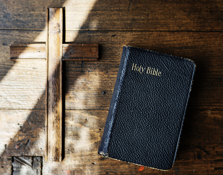 Sunlight on a Bible and wooden cross Stock Photo