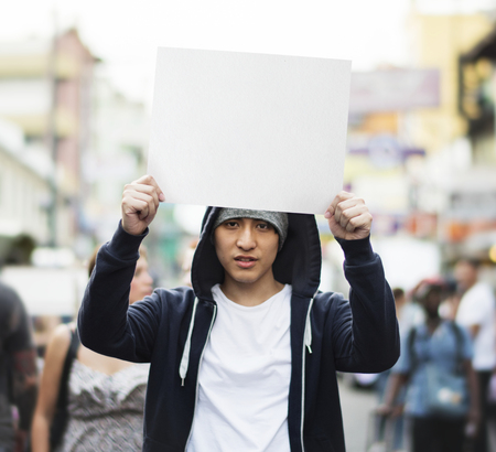 Young asian guy with a blank placard