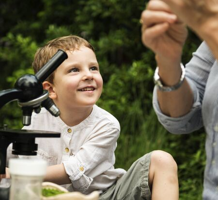 Young boy learning with outdoors with a telescope