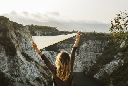Woman arms raised and holding flag on mountain Banco de Imagens