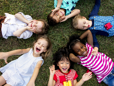 Group of kindergarten kids lying on the grass at park and relax with smiling Stockfoto