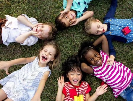 Groep kleuterschooljonge geitjes die op het gras bij park liggen en met het glimlachen ontspannen Stockfoto