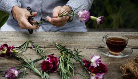 花屋の手は花の葉をトリミング