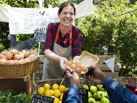 Groenteboerder verkoopt organisch vers landbouwproduct op boerenmarkt Stockfoto
