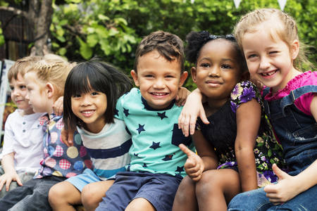 groupe d & # 39 ; amis de maternelle enfants assis assis et souriant en plein air