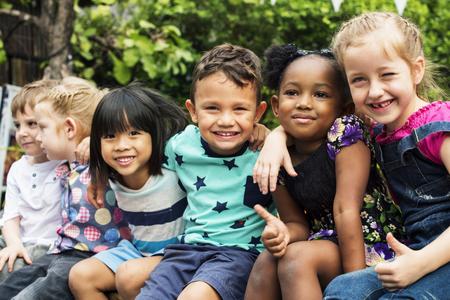 Grupo de niños de kindergarten amigos brazo sentados y sonriendo diversión
