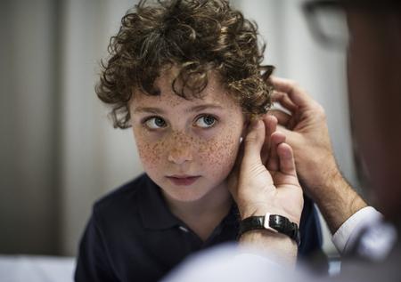 그의 귀를 검사하는 젊은이 스톡 콘텐츠
