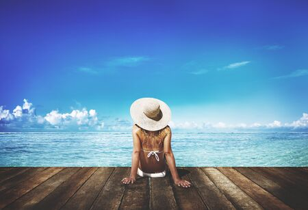 Woman tanning on a deck next to the beach Stock Photo