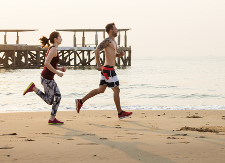 The couple is running at the beach together