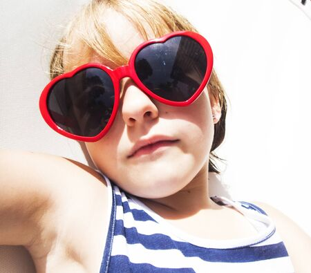 Closeup of young caucasian girl sunbathing with sunglassses