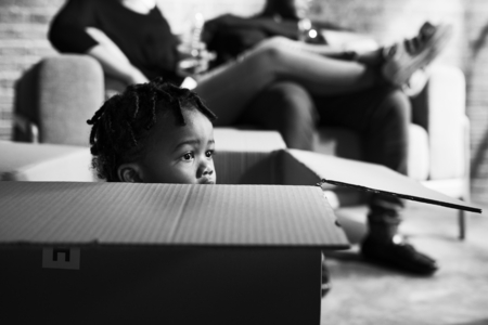 African kid playing inside a box Stock Photo