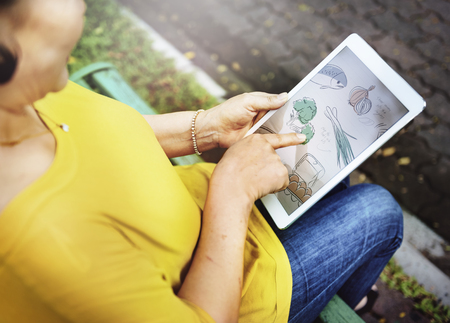 아시아 여자 공원에서 디지털 태블릿을 사용하고 있습니다 스톡 콘텐츠