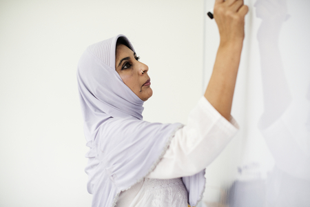 A Muslim teacher writing on a white board