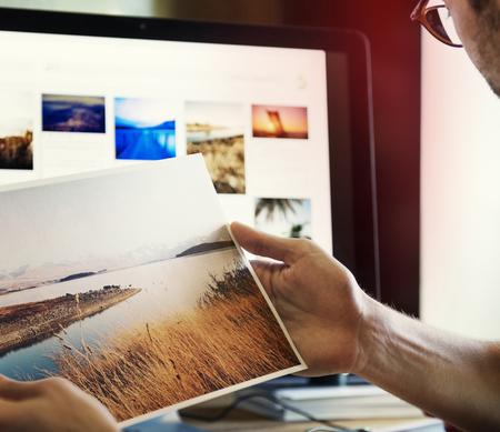 Ein Mann, der Fotos auf einem Computer bearbeitet Standard-Bild - 90271812