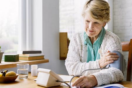 그녀의 자신의 맥박을 검사하는 노인 여성