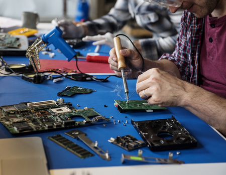 Hand soldering tin on electronics circuit board