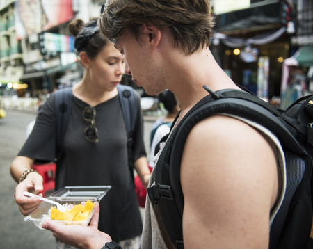 Tourists trying mango with sticky rice