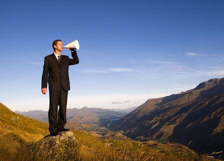 山の頂上に叫んでいるビジネスマン。