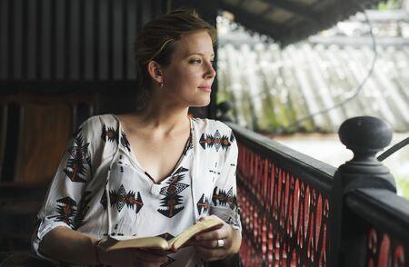 Caucasian woman reading the book at the balcony Stock Photo
