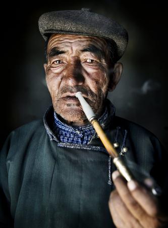 Mongolian man in traditional dress smoking a pipe. Фото со стока