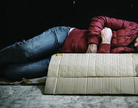 Homeless man sleeping on a cardboard concept
