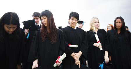 Group of diverse grads with caps and gowns in graduation ceremony