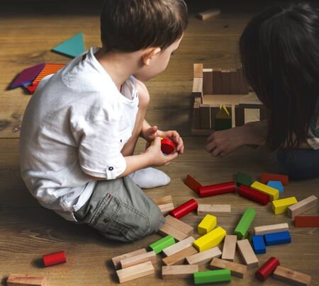 Children having fun playing toy blocks