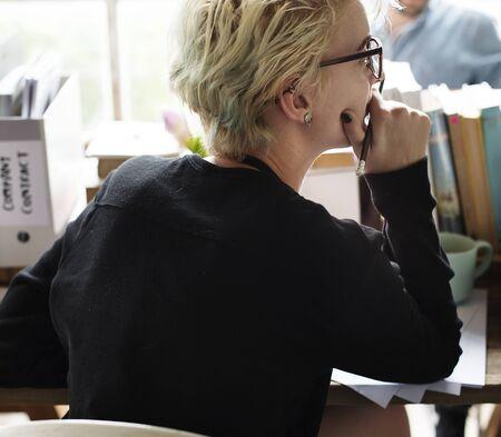Blonde woman contemplating at her desk Banco de Imagens