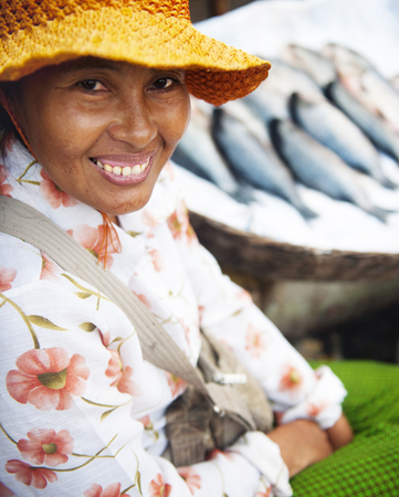Indigenous Cambodian woman selling fish at a market.