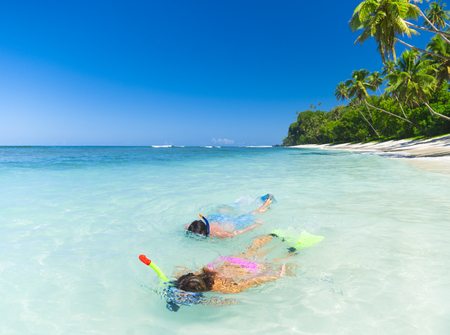 Couple snorkeling by the shore Stock Photo