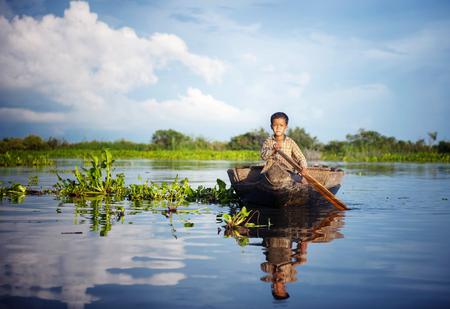 캄보디아 소년 그의 부동 마에서 보트 여행.