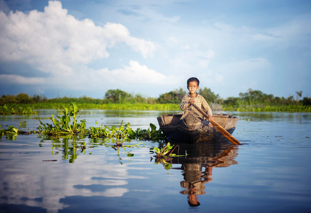 Cambodian boy traveling by boat in his floating village. Reklamní fotografie