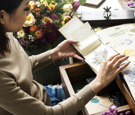 Woman looking a dried flower book Imagens