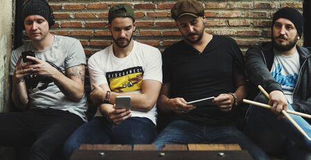 Adult Men Sit Together Use Mobile Phone Banco de Imagens