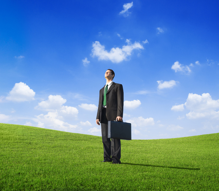 Businessman on a green field concept Stock Photo