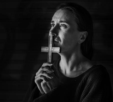 Mujer sosteniendo Cruz orando por Dios Foto de archivo - 89682339